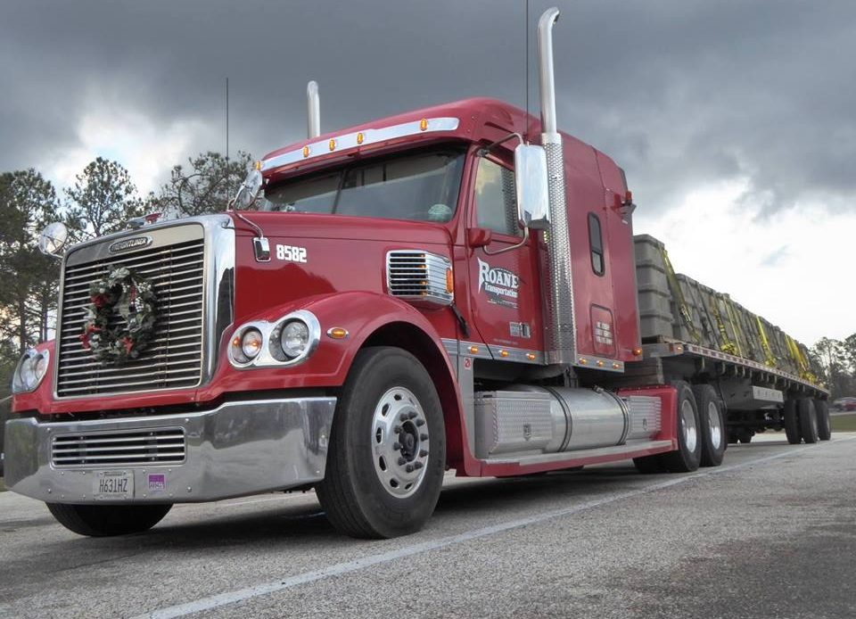 red Roane Transportation truck and flatbed trailer